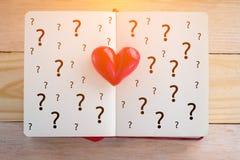 Réservez avec les pages et le coeur ouverts d'argile avec le symbole de point d'interrogation Images libres de droits