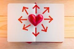 Réservez avec les pages ouvertes et la forme de coeur d'argile au milieu Images stock