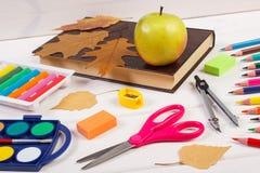 Réservez, des accessoires d'école et des feuilles automnales sur les conseils blancs, de nouveau au concept d'école Images libres de droits