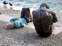 Réservez la lecture sur un lac près d'une statue en bronze triste masculine Image stock