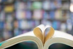 réservez la page dans la forme de coeur avec le fond de bibliothèque, amour dans valent Images libres de droits