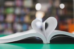 réservez la page dans la forme de coeur avec le fond de bibliothèque, amour dans valent Photographie stock