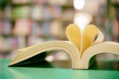 réservez la page dans la forme de coeur avec le fond de bibliothèque, amour dans valent Photo libre de droits
