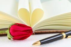 Réservez les pages pliées dans une forme et des roses de coeur avec le stylo Photos libres de droits