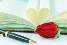 Réservez les pages pliées dans une forme et des roses de coeur avec le stylo Images libres de droits