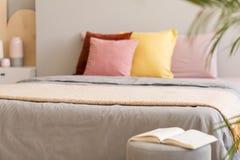 Réservez sur des selles à côté du lit gris avec les oreillers couvrants et colorés dans l'intérieur de chambre à coucher Vraie ph photographie stock libre de droits