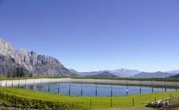 Réservoir d'eau devant le panorama de montagne Photographie stock