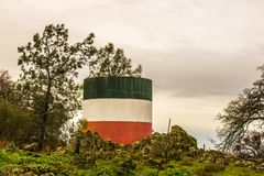 Réservoir d'eau peint avec des couleurs italiennes de drapeau en sierra collines Image libre de droits