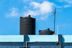 Réservoir d'eau sur le toit au-dessus du ciel bleu photographie stock libre de droits