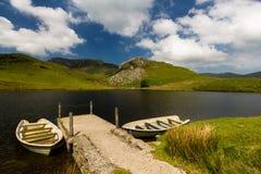 Réservoir de Llyn y Dywarchen avec deux bateaux à rames par la jetée, Snowd photos libres de droits