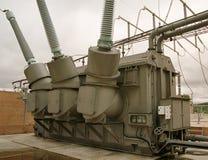 Réservoir de transformateur et tourelles à haute tension et ciel gris Photos stock
