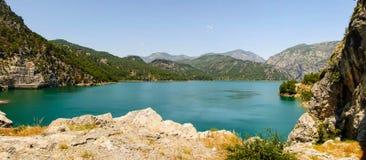 Réservoir parmi des montagnes avec de l'eau clair vert Images stock