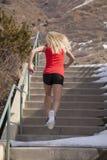 Réservoir rouge de femme couru vers le haut de la neige d'escaliers photo libre de droits