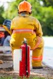 Réservoir rouge du feu, de sapeur-pompier avec le feu et de costume pour se protéger image libre de droits