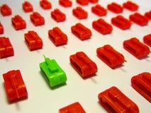 R?servoir vert de jouet vis-?-vis des rang?es des r?servoirs rouges de jouet pour symboliser Brexit et d?saccord politique photo stock