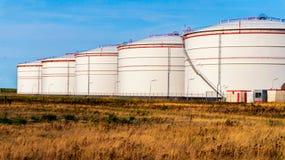 Réservoirs blancs dans la ferme de réservoir avec le ciel bleu photographie stock