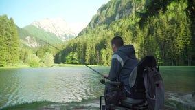 résolution 4k de pêcheur handicapé dans un fauteuil roulant électrique pêchant dans le beau lac près de la forêt et de la montagn banque de vidéos