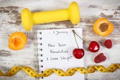 Résolutions de nouvelle année écrites en carnet, haltères, centimètre et nourriture saine Image libre de droits