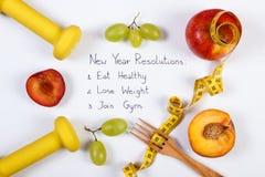 Résolutions de nouvelle année, fruits frais, haltères et centimètre, nourriture saine et concept de mode de vie Photos stock