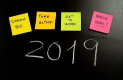 Résolutions de nouvelle année ou notes collantes de but et colorées populaires de post-its sur le tableau noir de craie images stock