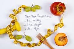 Résolutions ou buts de nouvelle année, fruits, haltères et centimètre, nourriture saine et concept de mode de vie Photographie stock libre de droits