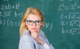 Résolvez la tâche de mathématiques La femme de professeur pensent à la solution et au résultat Salle de classe futée de professeu photo stock