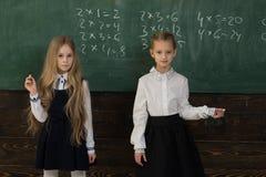 Résolvez le problème deux écolières résolvent le problème à l'école résolvez le problème à la leçon d'école s'aider à résoudre photo stock