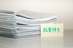 Résultat de attente ; Pile de documents sur le bureau et le fond blancs Images libres de droits