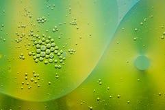Résumé d'huile d'olive flottant sur l'eau avec le vert, turquoise images stock