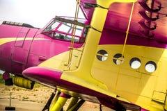 Résumé, vieux jaune, rose, avion pourpre dans l'aéroport abandonné à côté de la forêt foncée dans un jour obscurci Photographie stock