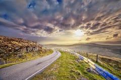 Rétrécissez la route pavée et un coucher du soleil dans un comté Kerry Image libre de droits