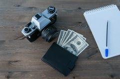 Rétro appareil-photo, bourse et bloc-notes avec le stylo sur une table en bois photo libre de droits