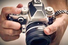 Rétro appareil-photo de SLR dans des mains Photographie stock