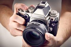 Rétro appareil-photo de SLR dans des mains Image stock