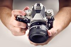 Rétro appareil-photo de SLR dans des mains Photographie stock libre de droits