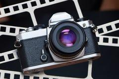 Rétro appareil-photo de SLR sur le fond du film de perforation Images libres de droits