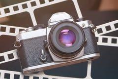 Rétro appareil-photo de SLR sur le fond du film de perforation Photographie stock