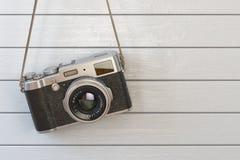 Rétro appareil-photo de photo de vintage accrochant sur le mur en bois blanc Images stock