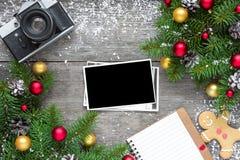 Rétro appareil-photo et cadre vide de photo de Noël avec des branches d'arbre de sapin, des décorations et le carnet rayé Photos stock