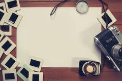 Rétro appareil-photo et quelques vieilles photos sur la table en bois image stock