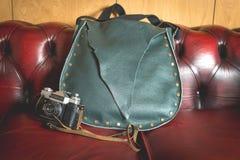 Rétro appareil-photo et sac à main sur le sofa rouge images stock