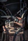 Rétro atelier de réparation de bicyclette avec des outils, des roues et le tube photographie stock libre de droits