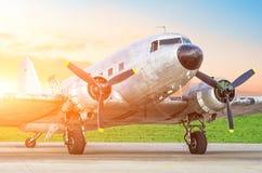 Rétro avion de turbopropulseur de cru, avec des moteurs sur les ailes, le soir au coucher du soleil à l'aéroport images stock