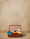 Rétro bagage de touristes avec les vêtements et le copyspace colorés Photographie stock