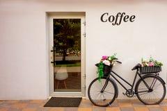 Rétro bicyclette comme décoration de parterre en dehors d'élément de café Séjours âgés noirs de vélo contre le mur avec le jardin image stock