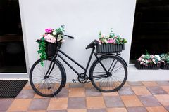 Rétro bicyclette comme décoration de parterre en dehors d'élément Séjours âgés noirs de vélo contre le mur avec deux paniers de j images stock