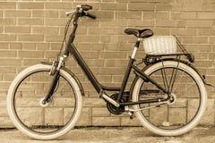 Rétro bicyclette noire de vintage avec le vieux mur de briques Photographie stock