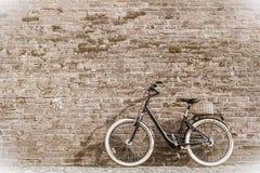 Rétro bicyclette noire de vintage avec le vieux mur de briques Photographie stock libre de droits