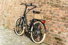 Rétro bicyclette noire de vintage avec le vieux mur de briques Image libre de droits