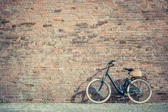 Rétro bicyclette noire de vintage avec le vieux mur de briques Photos libres de droits